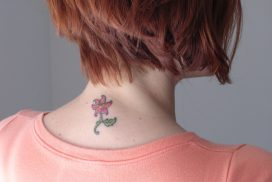 woman with a flower tattoo on her neck